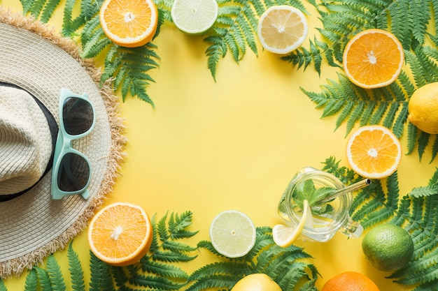 Sunhat femminile della paglia della spiaggia, occhiali da sole, citrici su giallo.