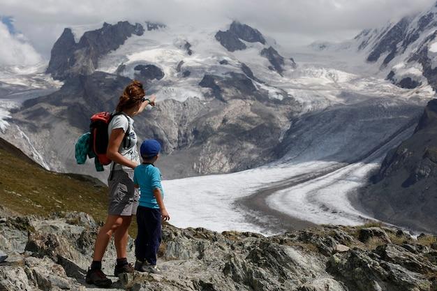 Sunnegga, svizzera - 15 agosto 2018: famiglia monoparentale, madre e figlio, durante le loro vacanze ai margini di una montagna ammirando un ghiacciaio alpino in svizzera.