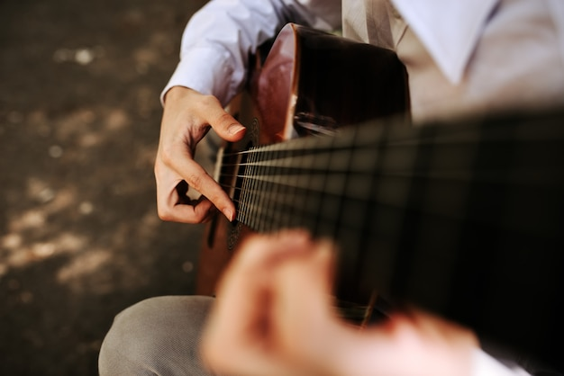 Suonando con la chitarra acustica all'aperto. macrofotografia.
