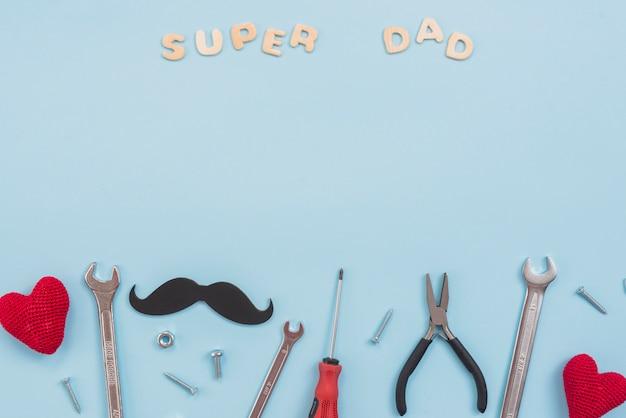 Super papà iscrizione con strumenti e baffi