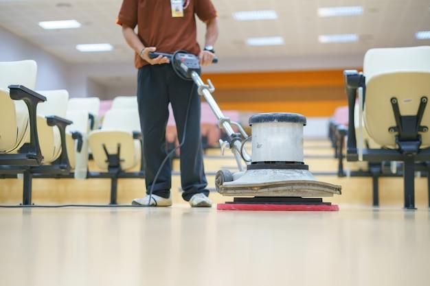 Superficie al suolo asiatica di pulizia del lavoratore