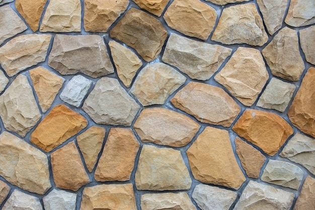 Superficie astratta della parete fatta dalle pietre della sabbia per uso come fondo.