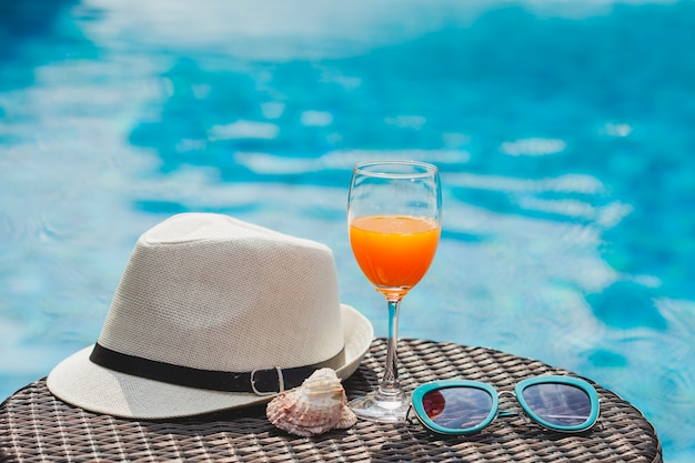 Superficie con bevande, occhiali da sole e cappello