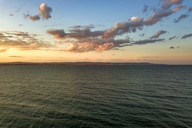 Superficie del mare con onde di acqua blu sotto il cielo al tramonto giallo e viola.