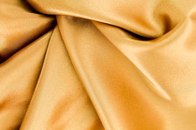 Superficie del materiale dorato con onde contorte