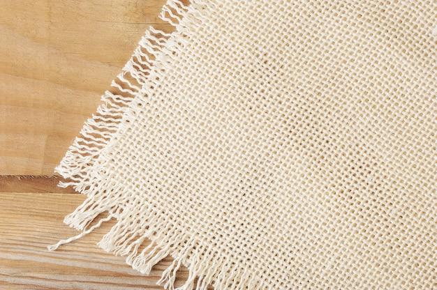 Superficie del panno di lino grezzo bianco su una tavola di legno