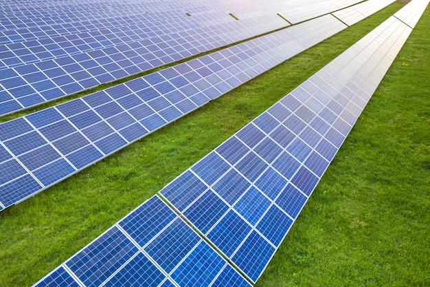Superficie del sistema fotovoltaico solare dei pannelli fotovoltaici che produce energia pulita rinnovabile su erba verde.