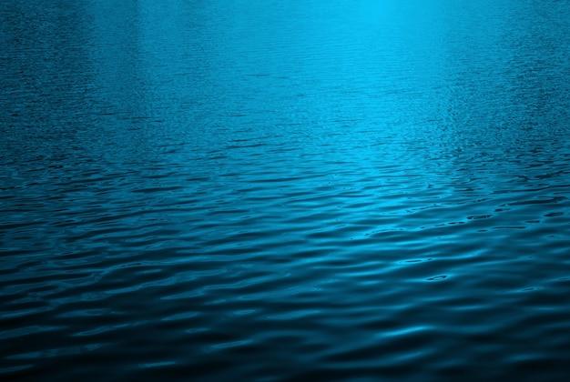 Superficie dell'acqua blu con riflessi di luce del sole brillante