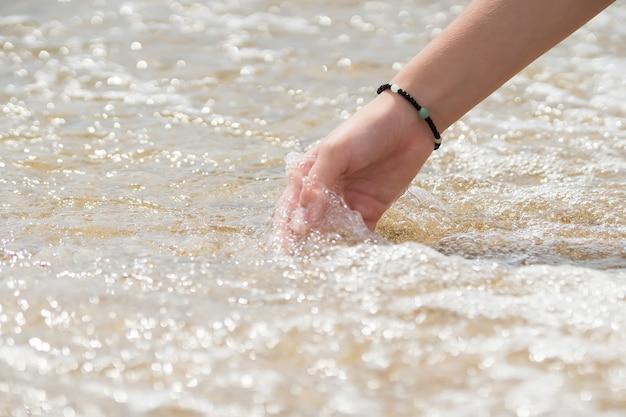 Superficie dell'acqua di tocco della mano della donna, puglia, mar ionio