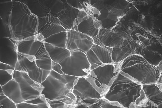 Superficie dell'acqua in bianco e nero con i riflessi luminosi del sole, acqua nel fondo della piscina