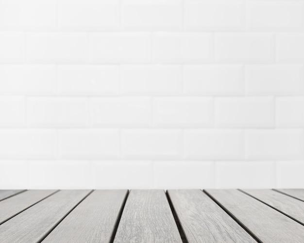 Superficie della tavola che si affaccia sul muro di mattoni bianchi sfocato