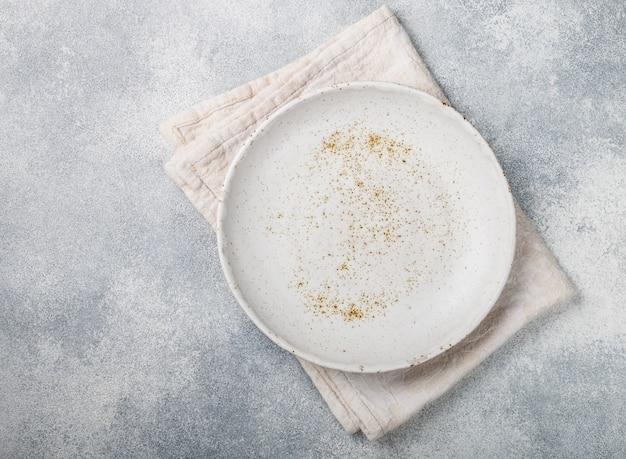Superficie di cottura con piatto luminoso vuoto e tovagliolo di lino sul tavolo di cemento grigio,