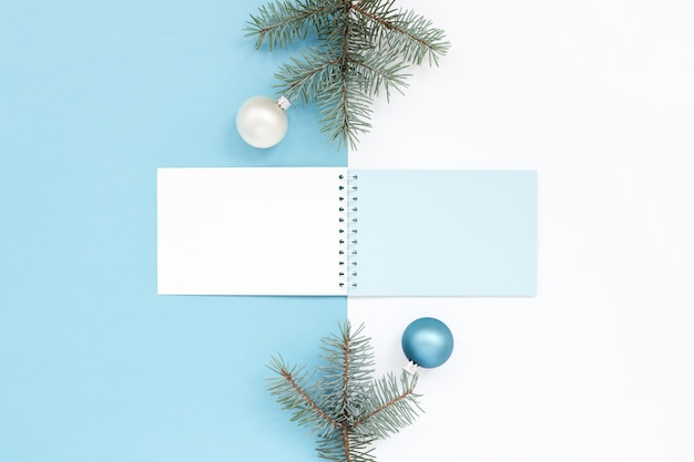 Superficie di festa di natale azzurro e bianco con blocco note e decorazioni