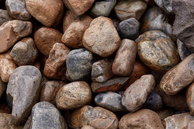 Superficie di molte pietre grezze bagnate dopo la pioggia