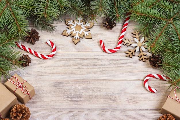 Superficie di natale con caramelle, regali e fiocchi di neve decorativi.
