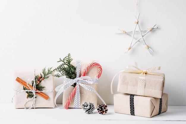 Superficie di natale con scatole regalo e decorazioni su un tavolo di legno bianco