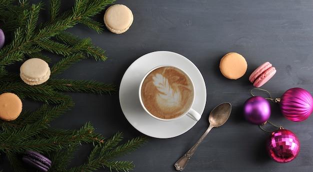 Superficie di natale con tazza di cappuccino con torta, macarons, giocattoli di natale e rami di alberi
