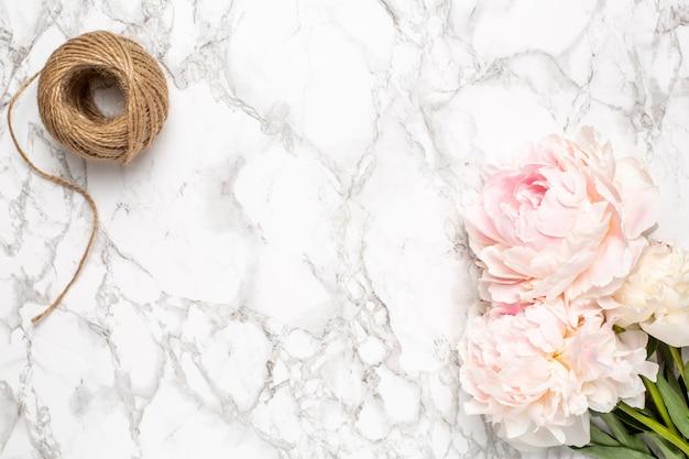 Superficie in marmo con fiori rosa peonia e spago