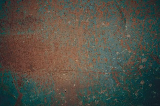 Superficie metallica arrugginita ricoperta di vernice incrinata