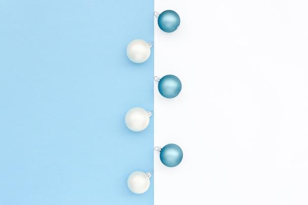 Superficie minimalista azzurra e bianca con palline di natale