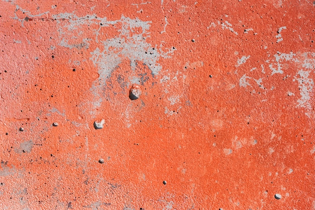 Superficie strutturata di un vecchio muro di cemento verniciato arancione.