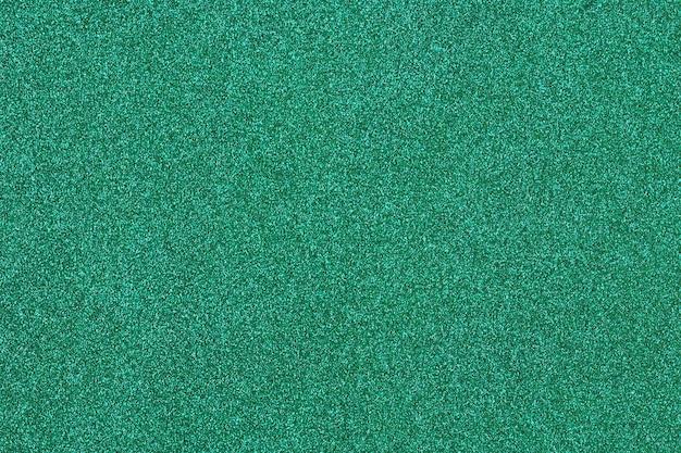 Superficie verde lucida piena di glitter oro lucido