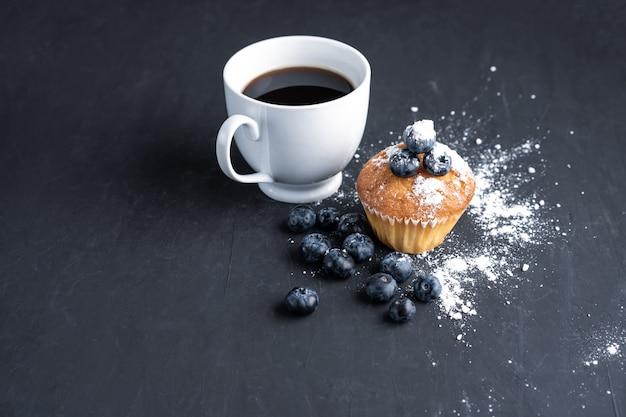 Superfood organico antiossidante ai mirtilli e muffin dolce con una tazza di caffè per un'alimentazione sana e un'alimentazione dietetica vista dall'alto su nero scuro