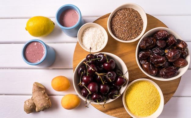 Superfoods in ciotole, frutta fresca, frullato di zenzero e frutti di bosco sul tavolo di legno bianco.