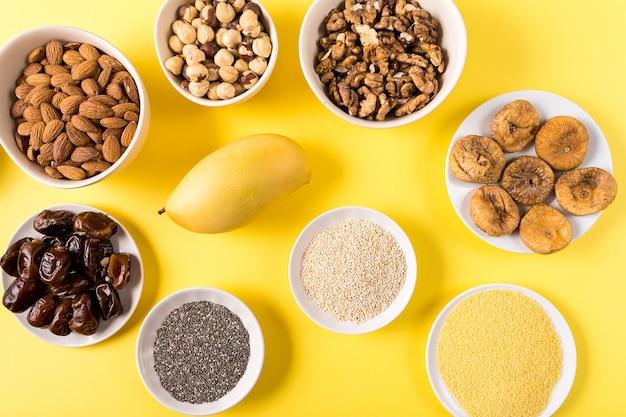 Superfoods in ciotole su sfondo giallo.