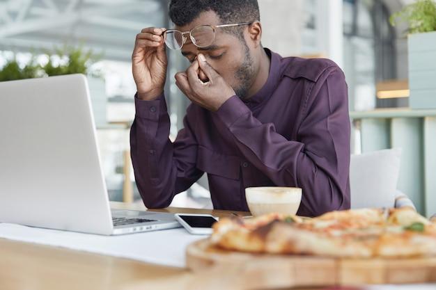 Superlavoro, concetto di stanchezza. impiegato maschio dalla pelle scura esausto si siede davanti al laptop, lavora a un nuovo progetto per lungo tempo, ha dolore agli occhi