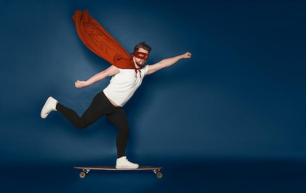 Superman cavalca su skateboard in mantello rosso sventolante e maschera sul retro blu