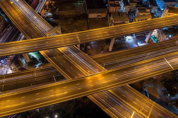 Superstrada massiccia di notte con la luce delle automobili, concetto industriale di trasporto
