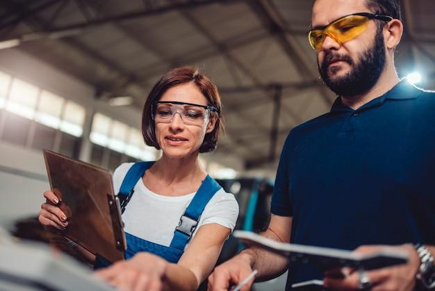 Supervisore che controlla il prodotto finale alla fabbrica con il lavoratore manuale