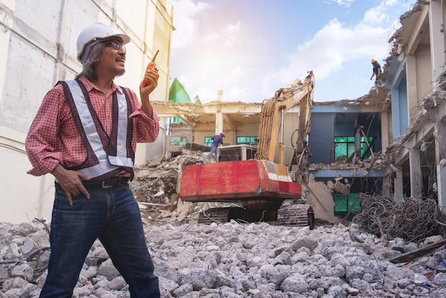 Supervisore dei controlli di demolizione o ingegnere, walky talky in mano sulla pila di mattoni