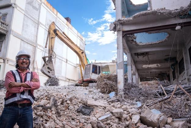 Supervisore del controllo di demolizione o ingegnere che sorride e ha attraversato le braccia sulla pila di mattoni