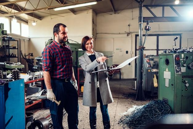 Supervisore della fabbrica che parla con l'impiegato nella fabbrica di fabbricazione