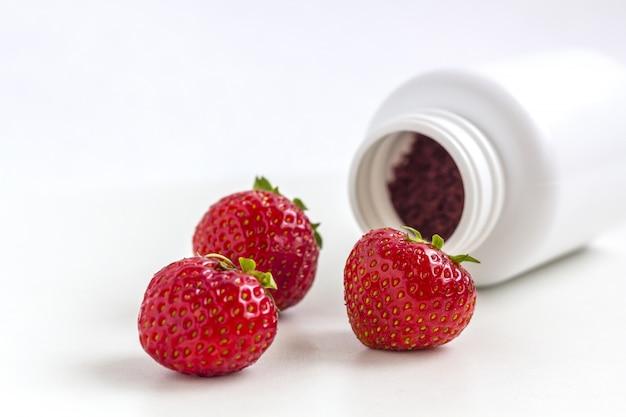 Supplementi di vitamine in capsule con bacche dal vaso di medicina.