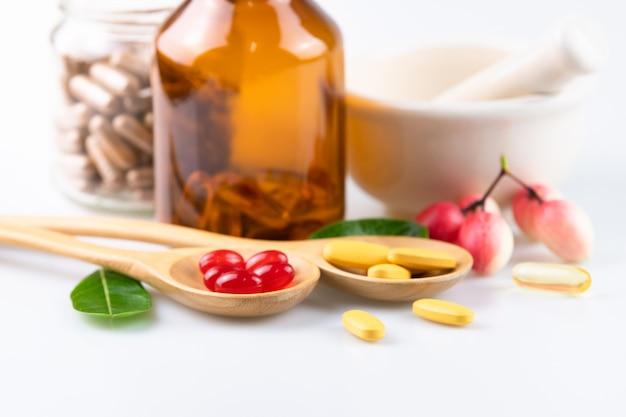 Supplementi organici della medicina alternativa, della compressa di pillole, della capsula e della vitamina su fondo bianco