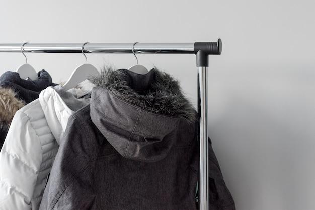 Supporto appendiabiti con giacche calde. giacche invernali con collo di pelliccia sono appese a grucce in legno bianche.