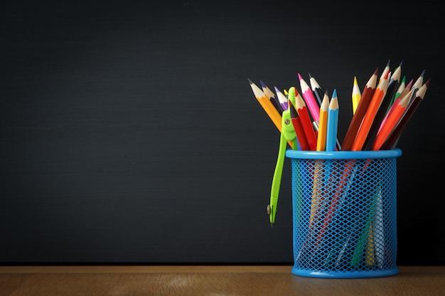 Supporto blu del primo piano con le matite della scuola sui precedenti di un grande bordo di gesso nero