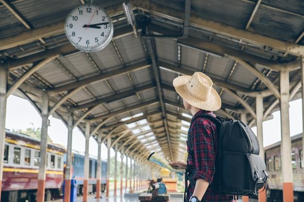 Supporto di viaggiatore con zaino e sacco a pelo sotto l'orologio nella festa di viaggio dei turisti della stazione ferroviaria concetto di viaggio viaggio dell'uomo