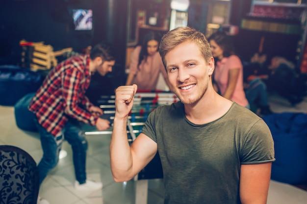Supporto felice del giovane nella stanza di gioco e posa sulla macchina fotografica. sorride e tiene la mano nel pugno. i suoi amici giocano a calcio balilla dietro.