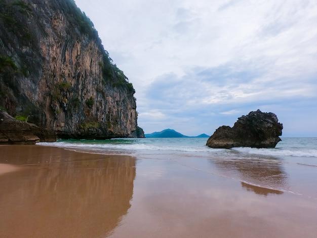 Surf costiero e schiuma bianca di acqua limpida in spiaggia sabbiosa.