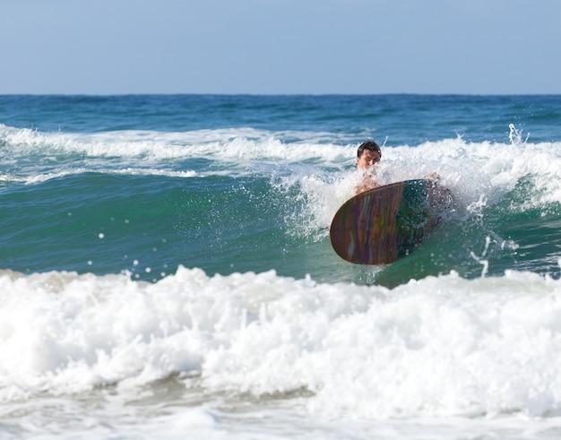 Surfer su longboard mentre cade tra le onde