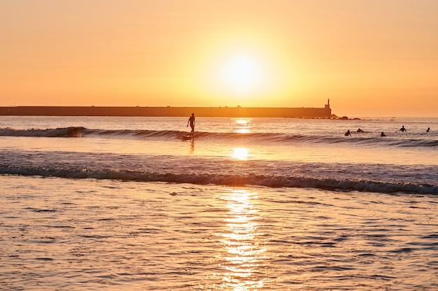Surfer surf su piccole onde in un pomeriggio soleggiato sulla costa con diversi surfisti in acqua