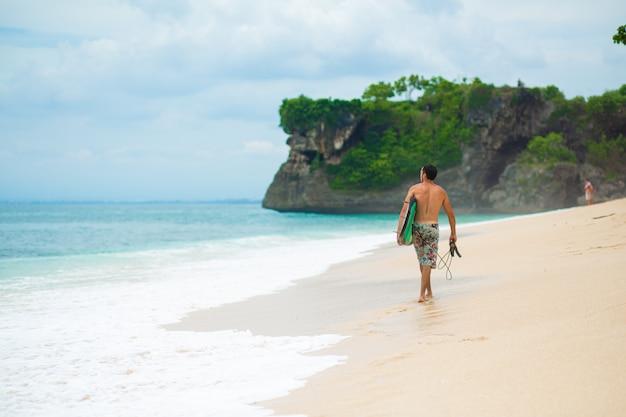 Surfer. uomo di surf con il surf che cammina sulla spiaggia tropicale di sabbia. stile di vita sano, attività acquatiche, sport acquatici. bellissimo oceano