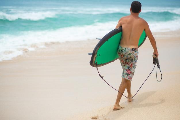 Surfer. uomo di surf con la tavola da surf che cammina sulla spiaggia tropicale di sabbia.