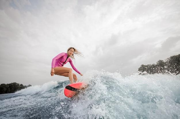 Surfista biondo della donna che guida giù l'onda di spruzzatura blu contro il cielo