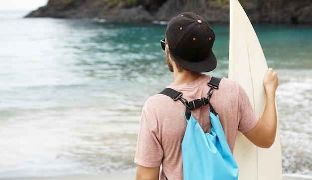 Surfista con tavola da surf rilassante sulla spiaggia dopo l'allenamento, guardando altri surfisti che praticano nuovi trucchi. colpo posteriore dell'uomo caucasico che gode della bella vista davanti a lui