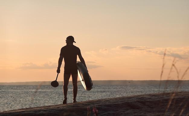 Surfista di paddleboard con tavola e pagaia va al lago. vista posteriore.